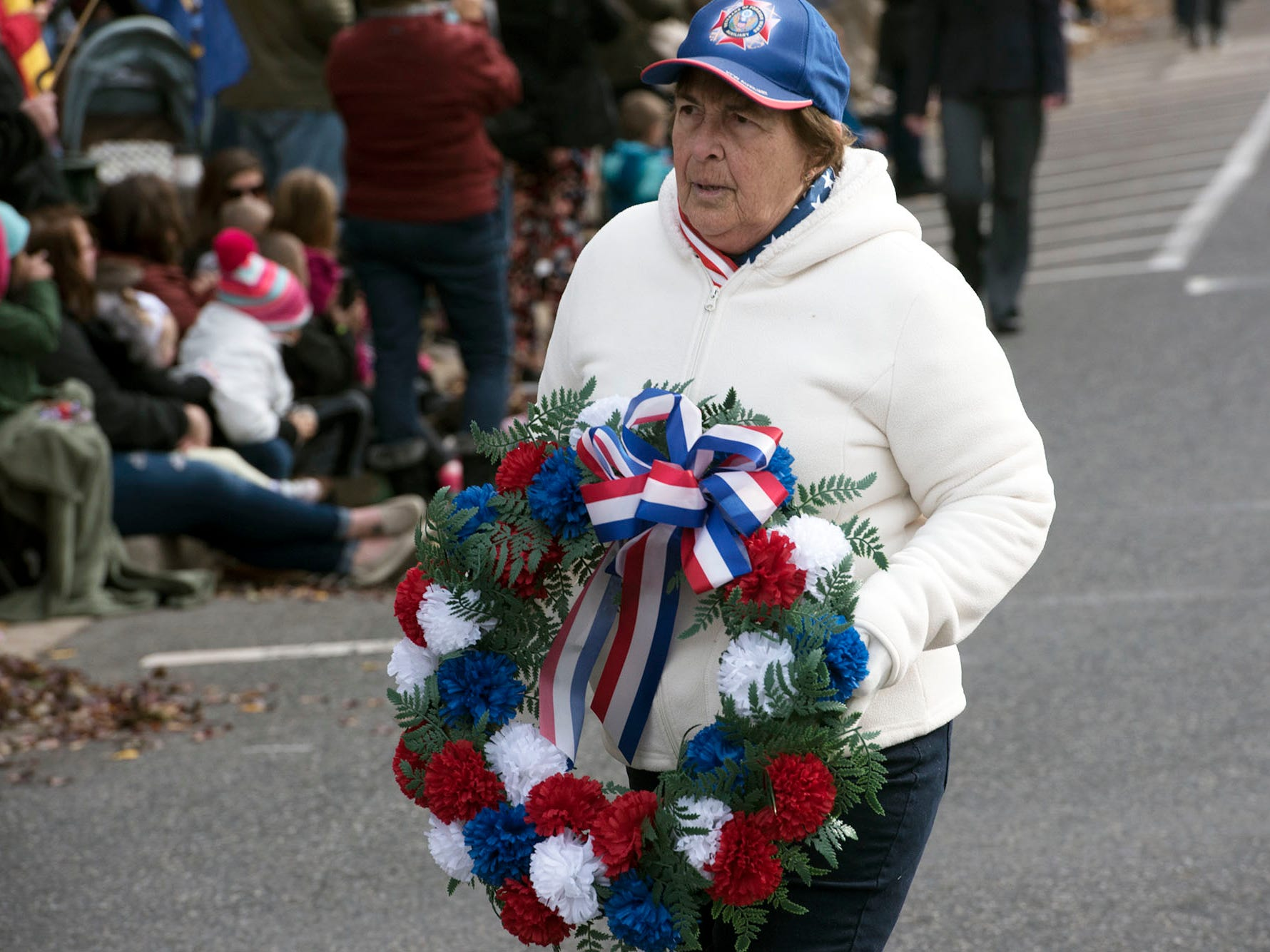 Julie Marker carries the wreath for Memorial Square. The Veterans Day Parade and ceremony to honor members of the military was held Monday, November 12, 2018 along Lincoln Way East and at Memorial Square.