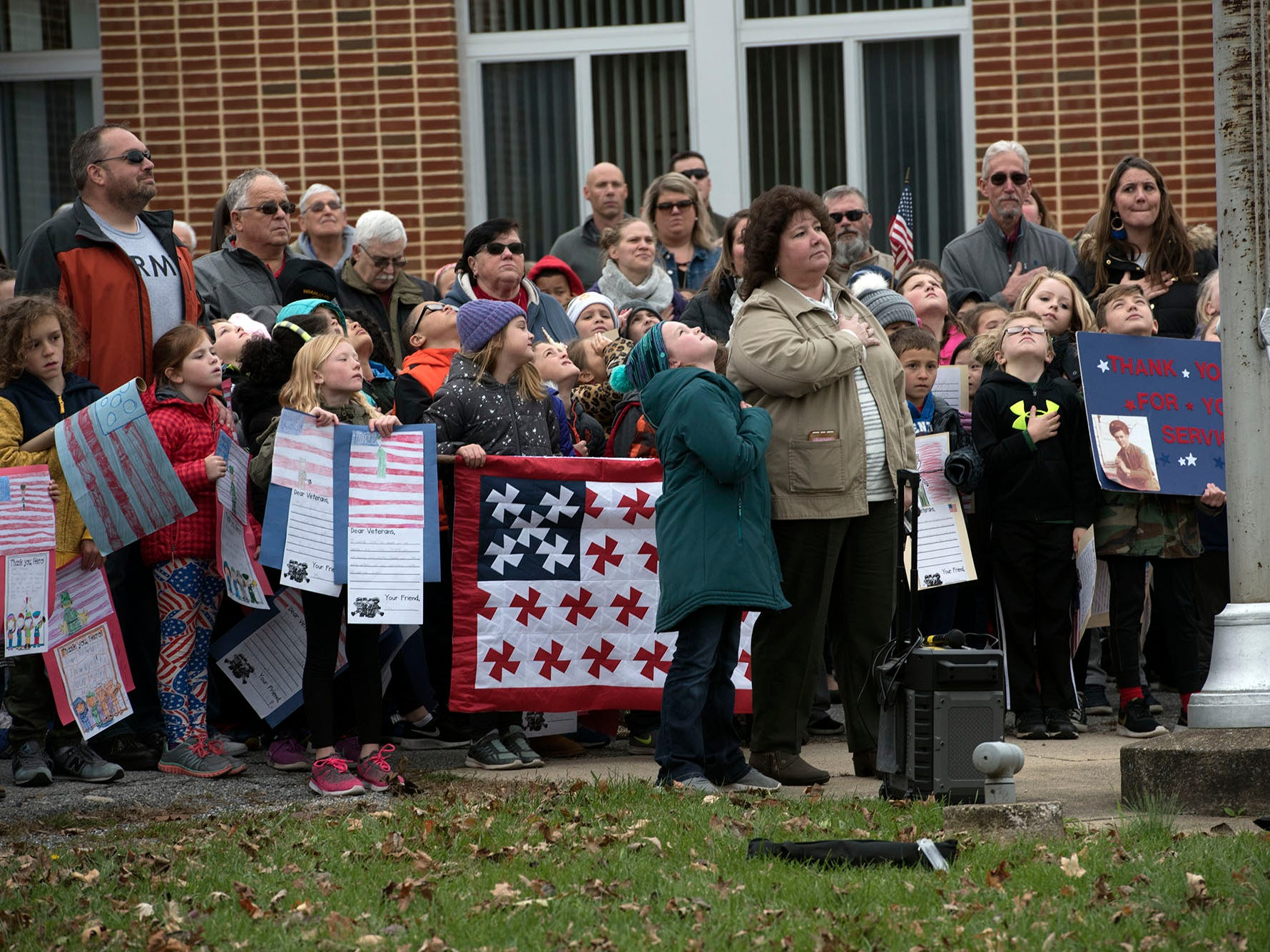 Students and teachers salute the flag during a Veterans Day Parade sponsored by James Burd Elementary School, Shippensburg. Last year, Burd hosted its own parade because the Shippensburg parade was canceled. Now the event is becoming a tradition.