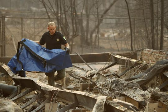 Sgt. Nathan Lyberger of the Yuba County Sheriff Department, prepares a bag to move human remains found at a burned out home at the Camp Fire, Sunday, Nov. 11, 2018, in Paradise, Calif. (AP Photo/John Locher)