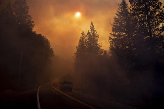 A vehicle drives through smoke from a wildfire near Pulga, Calif., Sunday, Nov. 11, 2018. (AP Photo/Noah Berger)