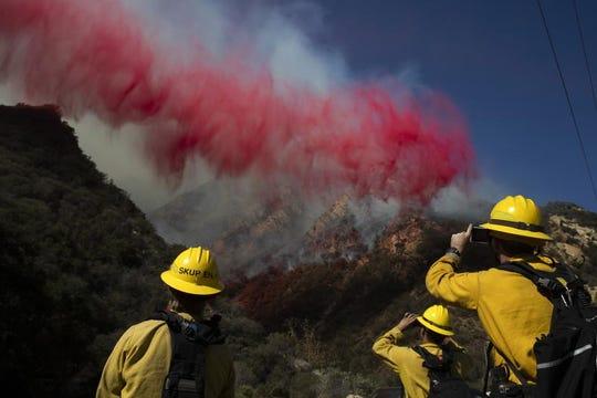 Firefighters take pictures of fire retardant dropped on a burning hillside Sunday, Nov. 11, 2018, in Malibu, Calif. (AP Photo/Jae C. Hong)