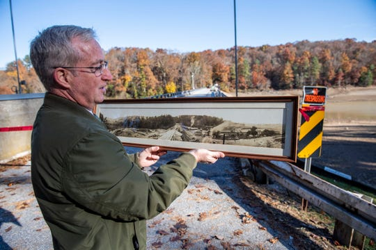 In this photo from after the draw down, JT Hand, chief operating officer for York Water Company, holds a panorama photo from the construction of the dam years ago at Lake Williams, taken within feet of where he stands.  The current project started in July of 2018.