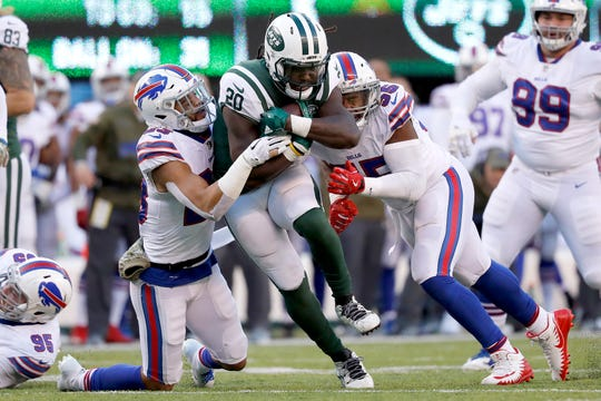 Micah Hyde, left, and Jerry Hughes, right, of the Buffalo Bills converge to tackle New York Jets running back Isaiah Crowell during the third quarter of the Bills' 41-10 victory Sunday at MetLife Stadium in East Rutherford, N.J.