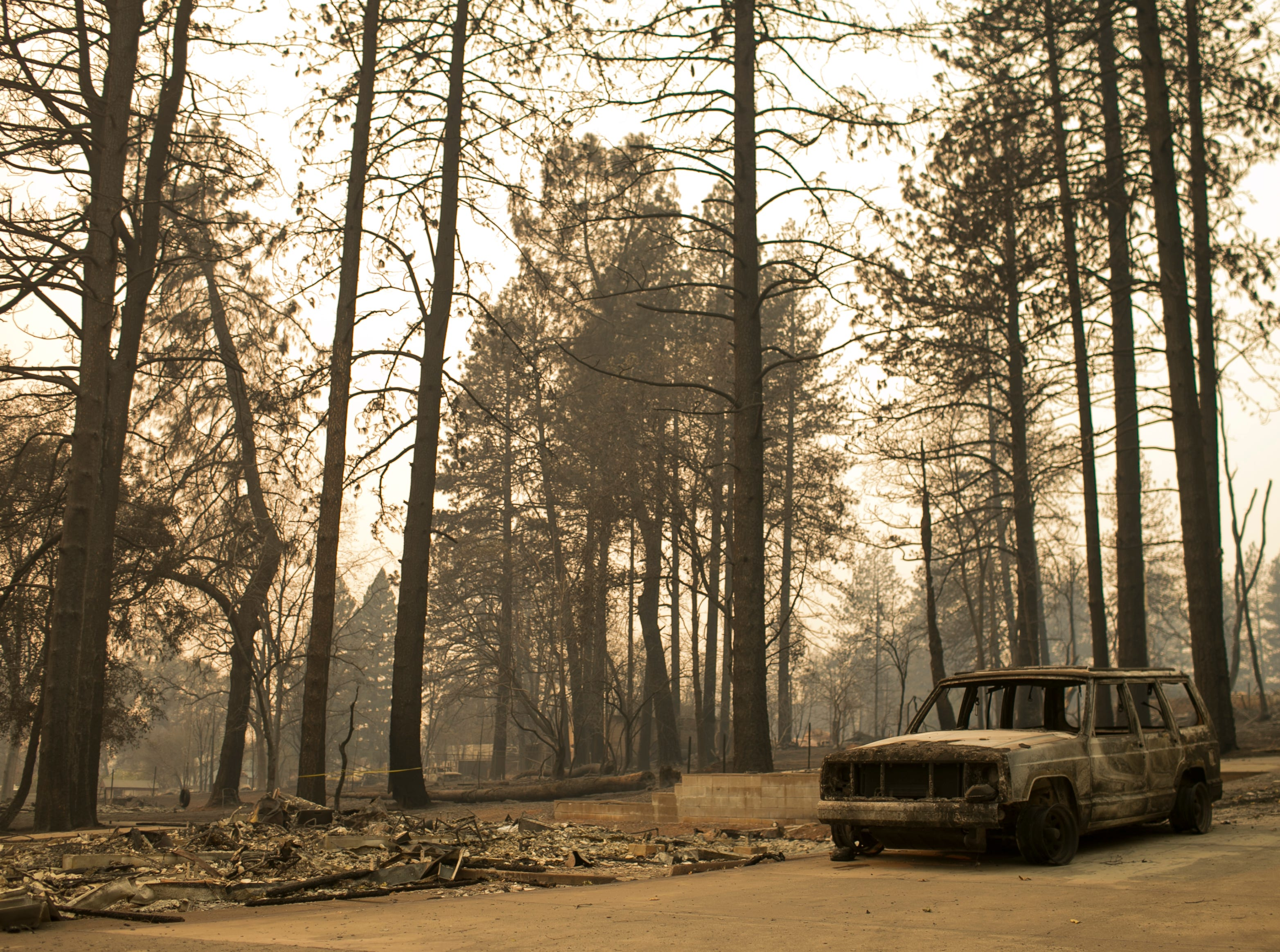 The remains of a home and a vehicle in its driveway sit empty days after the Camp Fire swept through town on Nov. 11, in Paradise, Calif.