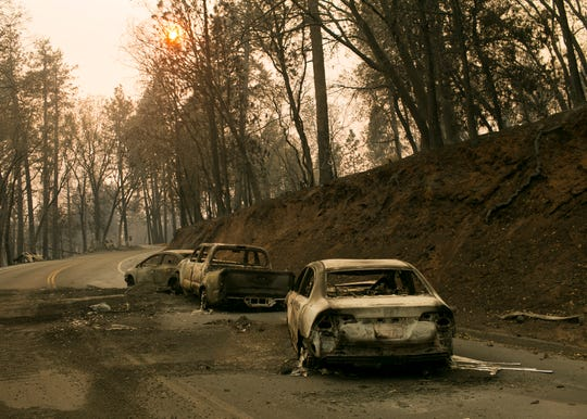Vehicles sit pushed off the road days after the Camp Fire swept through town on Nov. 11, in Paradise, Calif.