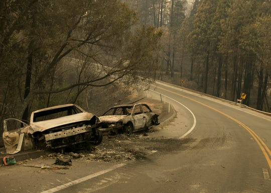 Vehicles sit pushed off the road days after the Camp Fire swept through town on Nov. 8 in Paradise.