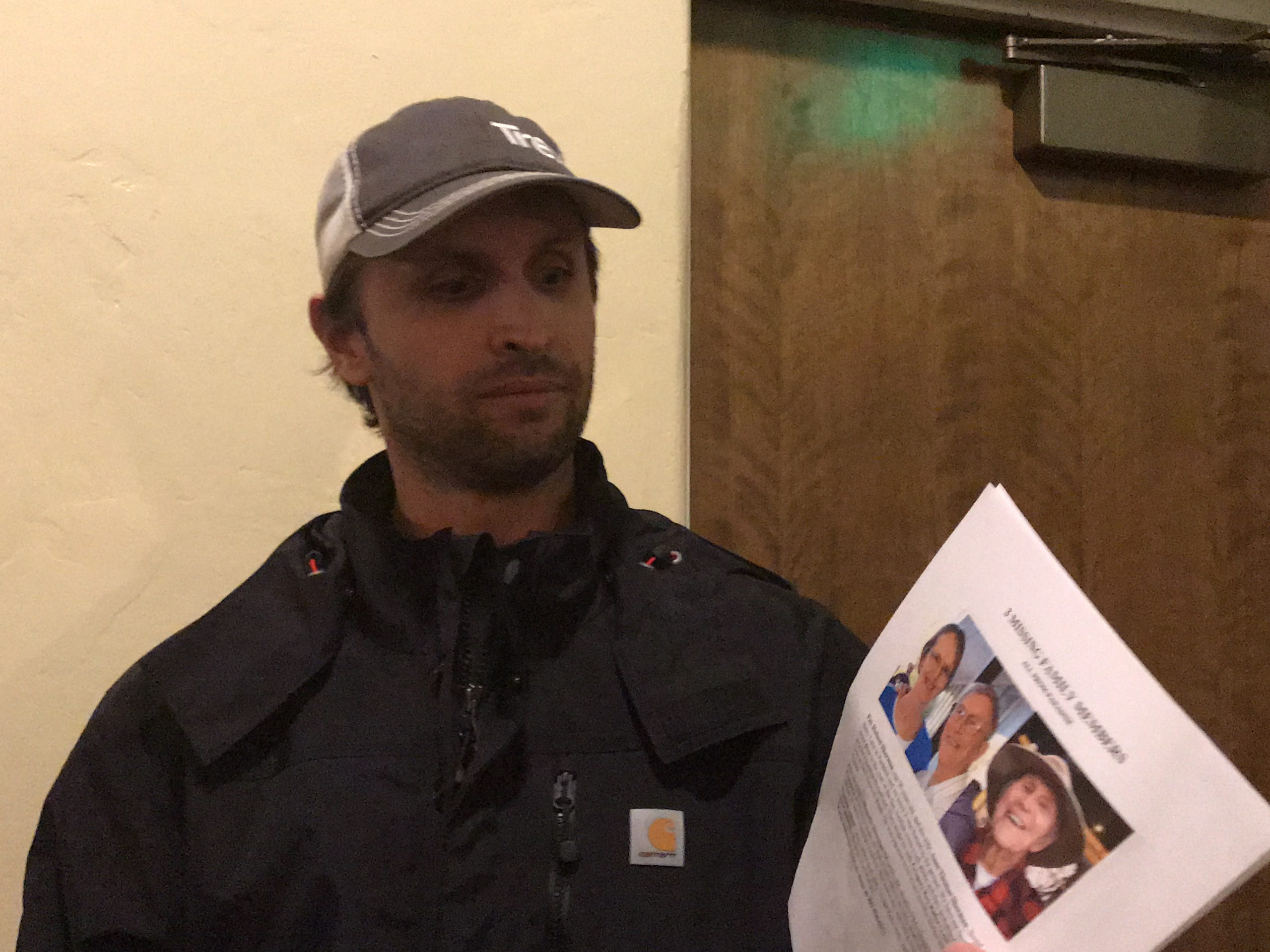 John Warner holds the flier his family made with photos of his missing grandparents.