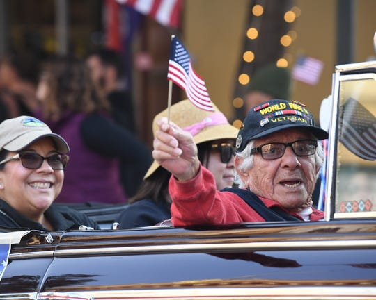 David Perez, a World War II veteran, holds a flag as he waves during Sunday's Monterey County Veterans Day Parade in Salinas.