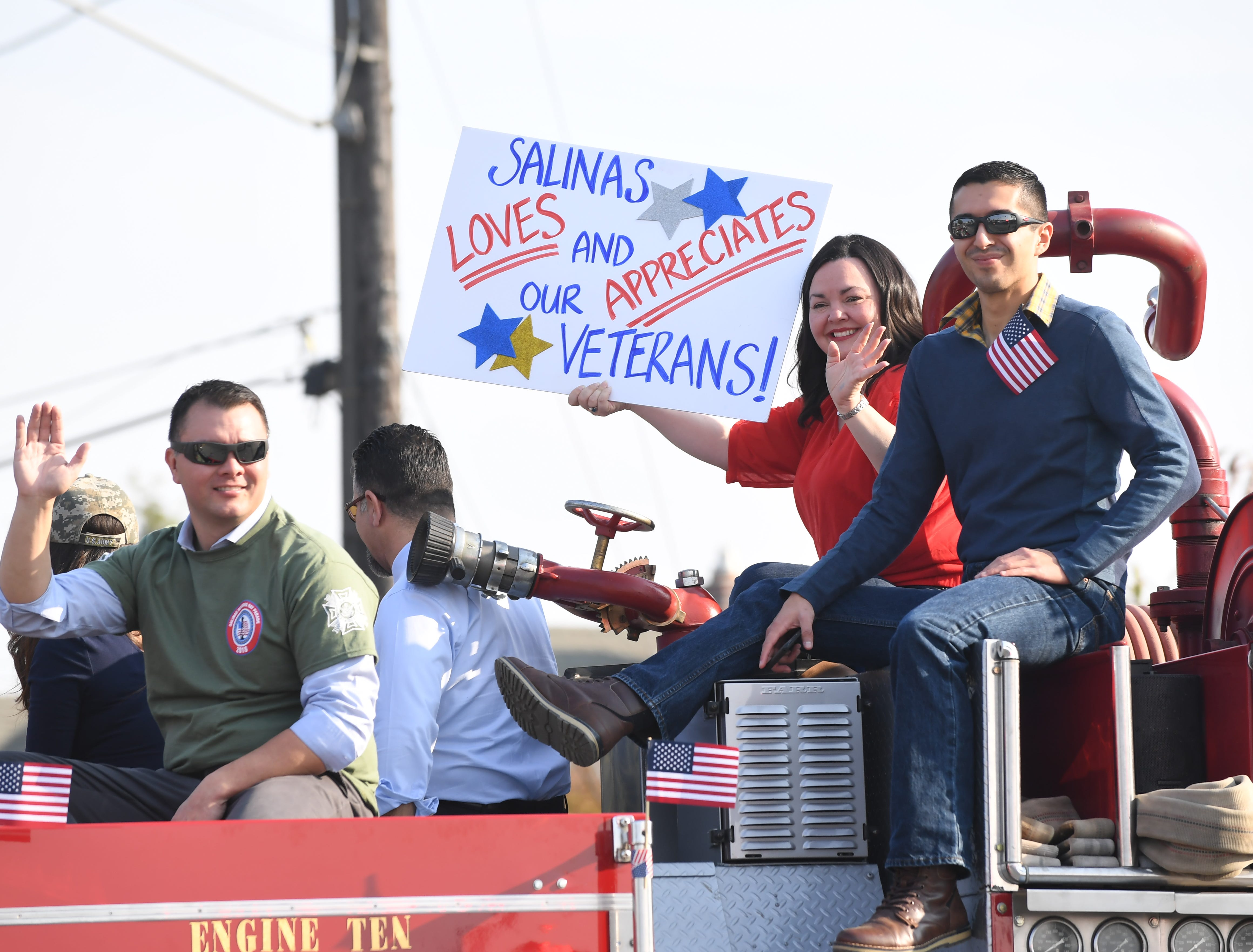 Councilman Scott Davis, far left, waves as Councilwoman Kimbley Craig, second to right, holds a sign honoring veterans at Sunday's Monterey County Veterans Day Parade in Salinas.