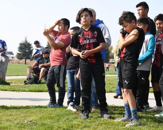 Jugadores de futbol y sus padres observan la colocación de la primera piedra del Complejo Regional de Fútbol de Salinas.
