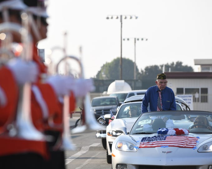 Lawrence Mosher, a veteran in the distance behind the Gonzales High School marching band, gets his vehicle ready for Sunday's Monterey County Veterans Day Parade.