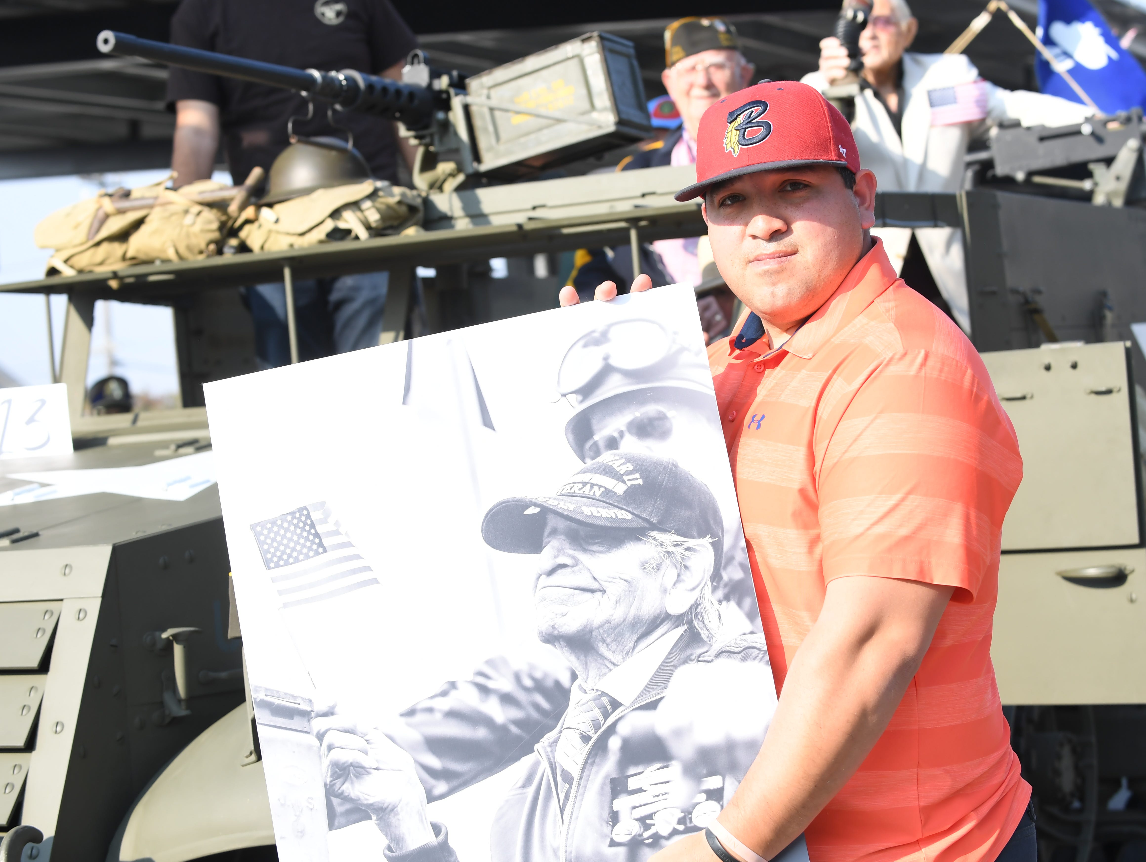 Efran Ruiz of Salinas holds a picture of his late grandfather, Juan G. Mejia, a World War II Army veteran, during Sunday's Monterey County Veterans Day Parade.