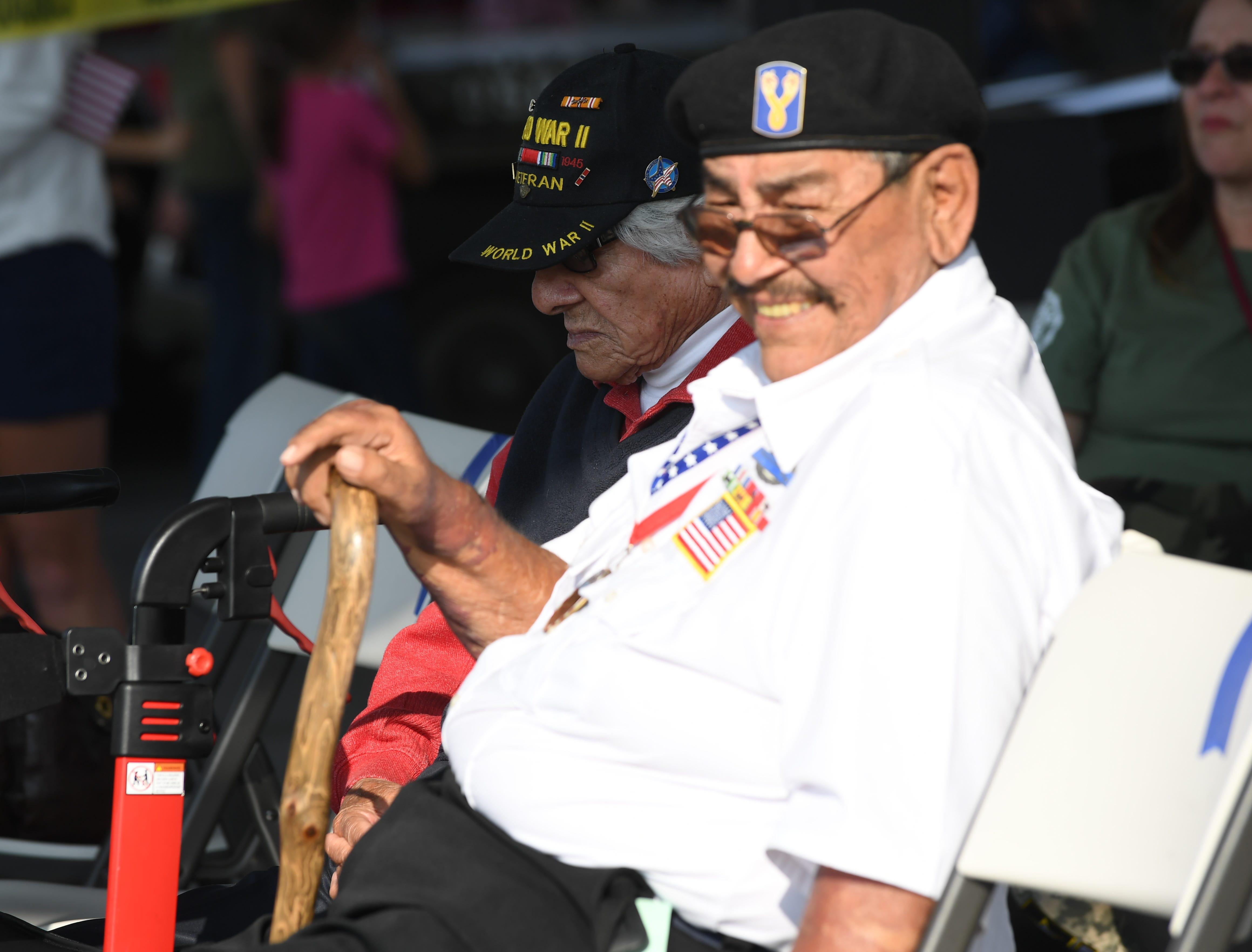 David Perez, left, a World War II veteran, sits with Salvador Armendariz, right, a Vietnam veteran, at Sunday's Monterey County Veterans Day Parade in Salinas.