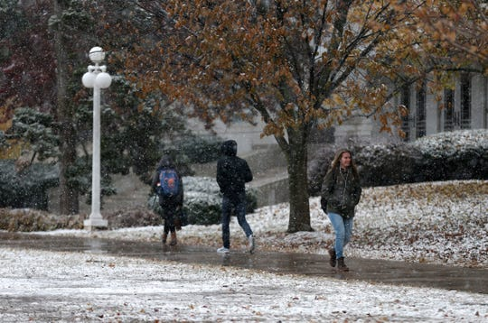 Students walk on the campus of Missouri State University as snow falls on Monday, Nov. 12, 2018.