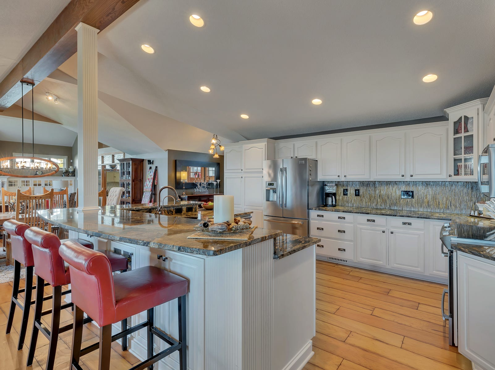 The kitchen features swirled granite countertops and stainless steel appliances.