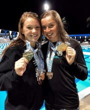 Chiles freshman Lydia Hanlon (left) and Jensen Beach freshman Blair Stoneburg celebrate gold medals at the FHSAA Class 3A state meet. Hanlon won the 100 backstroke and Stoneburg the 100 freestyle, both in All-American times.
