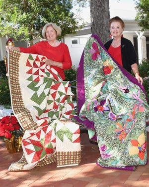 Displaying two handmade quilts to be raffled off are, from left, Christmas Tree Lane Co-chairs Joan Irvine and Maggie Fleming.