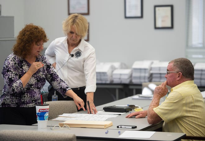 """Nineteenth Judicial Circuit Judge Kathleen Roberts (left) explains to observers in another room, the process of replacing a damaged ballot with a duplicated ballot, as the Martin County Elections Canvassing Board, including Martin County Supervisor of Elections Vicki Davis (center) and Commissioner Harold Jenkins, recount 78,571 ballots Monday, Nov. 12, 2018, at the Martin County Supervisor of Elections office in Stuart. The board plans to complete the recount Monday with the help of high-powered voting machines. """"We're going until we're done,"""" Davis said of the task. Secretary of State Ken Detzner ordered recounts in the elections for governor, U.S. Senator and agriculture commissioner because the results provided to the state from the margin from all three races were less than one-half of one percent."""