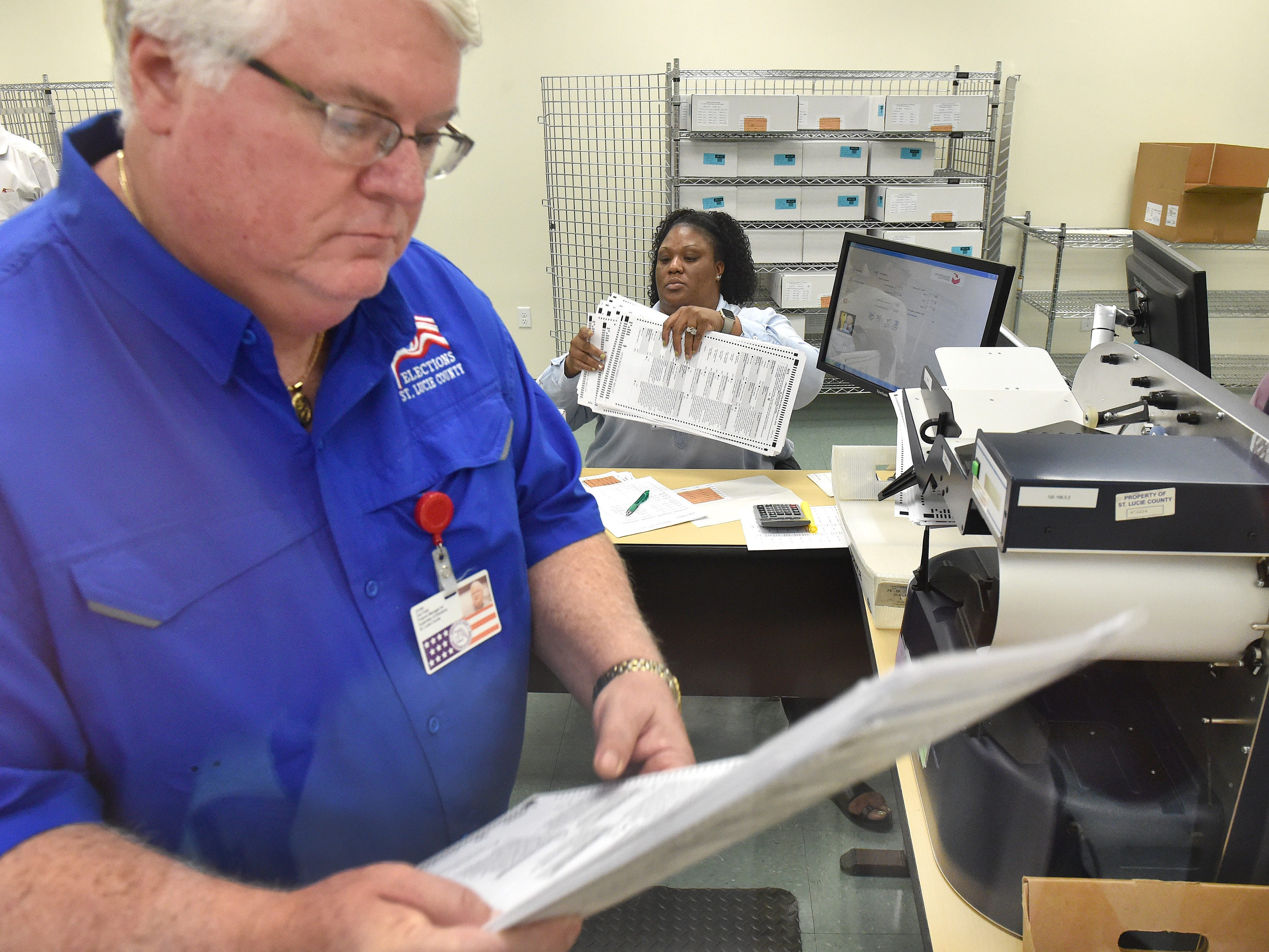 """St. Lucie County Supervisor of Elections staff members Dan Field (front), finance manager, and Natasha Bailey, elections system operator, are seen through a glass window separating the recount staff from the witnesses and media, as they help with a machine recount of 38,853 absentee ballots during the first day of Florida Secretary of State ordered machine recount of the Governor, U.S. Senate, and the Florida Commissioner of Agriculture contests, at the St. Lucie County Supervisor of Elections office Monday, Nov. 12, 2018, in Fort Pierce. """"It's important to do this because every vote counts,"""" said Gertrude Walker, St. Lucie County Supervisor of Elections. """"And this is an example of us really trying to determine who won the election and making sure every vote did count."""""""