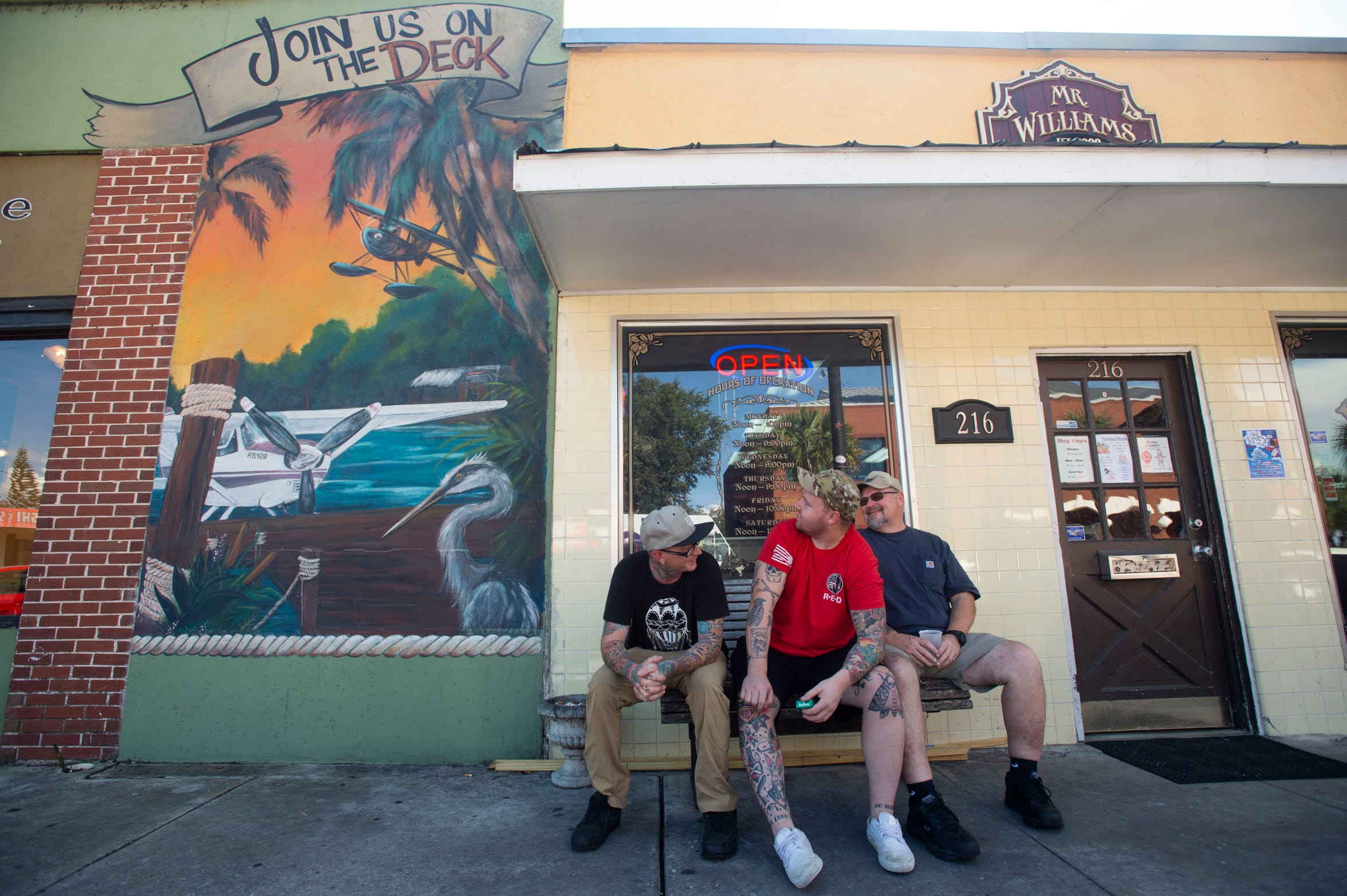 """Mr. Williams Tattoo Co. artist Kent Marvel (left) and clients Stephen Malmrose and Ray Malmrose, all of Tavares, enjoy a break outside near a seaplane mural Thursday, Nov. 8, 2018, in Tavares. """"Everywhere you look, you'll see a little seaplane. That's why we moved here,"""" Kent said, noting the business opened in 2005 and moved to Main Street in 2008 because of the city's rejuvenation."""