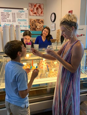 Meghan Visconte and Colin Krakowski sample flavors before making their final selection. Meghan decided on 'h-la-la,' while Colin enjoyed 'Safari.' Store owner Livia Sorger and employee Madison Griscom look on.