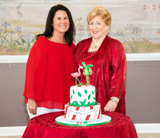 Chair Lisa Pinkley, left, and Founding Chair Polly Pharo celebrate the 10th anniversary of the Woman's Club of Stuart's Home Tour with a Florida-style holiday cake.