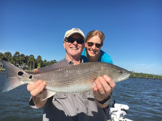 Jerry and Lindy showing off a nice slot redfish that he caught while fishing docks along the Indian River in Fort Pierce.