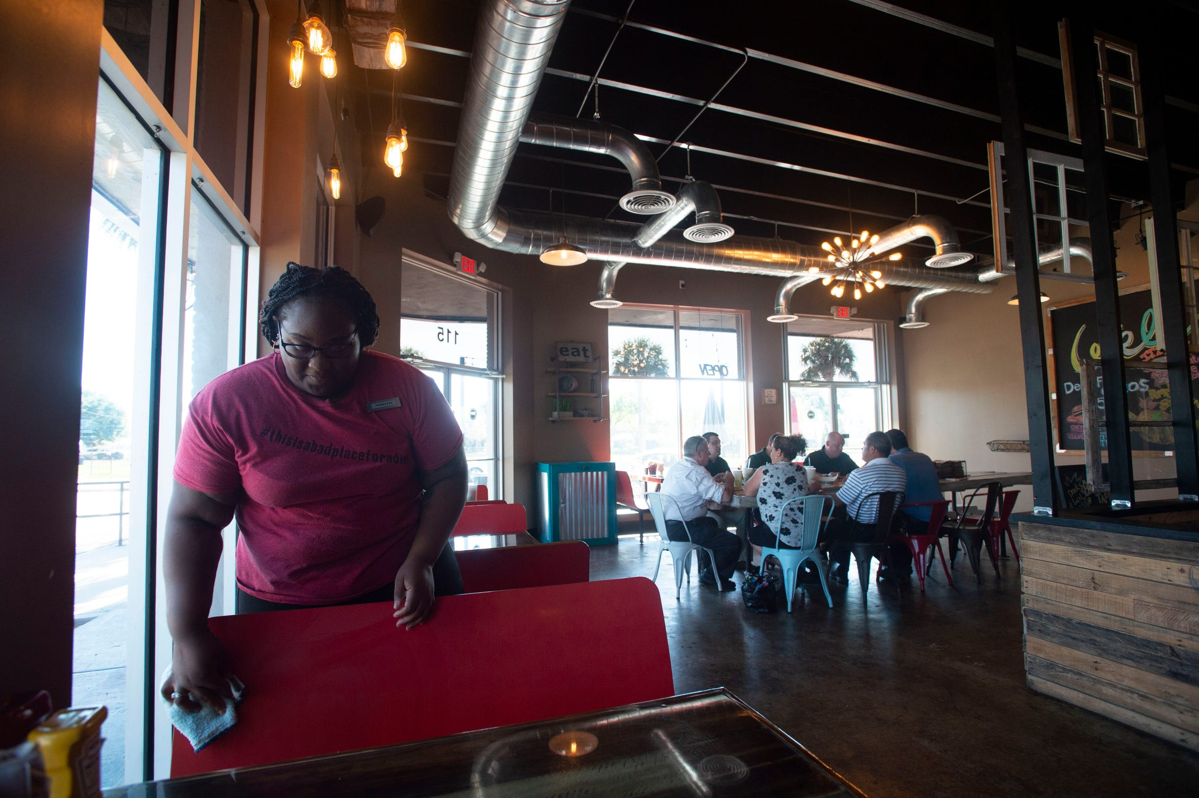 """BTW-Burgers Tacos Waffles employee Nisha Hughes, of Tavares, cleans the dining room at the recently opened restaurant Thursday, Nov. 8, 2018, in Tavares. Multiple restaurants, hotels and a seaplane manufacturer have opened since the central Florida town, nicknamed """"America's Seaplane City,"""" embraced the unique travel option."""