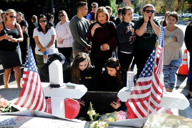 A group of people visit the Borderline Bar & Grill memorial Monday in Thousand Oaks. Twelve people were killed Wednesday night by a gunman who later took his own life.