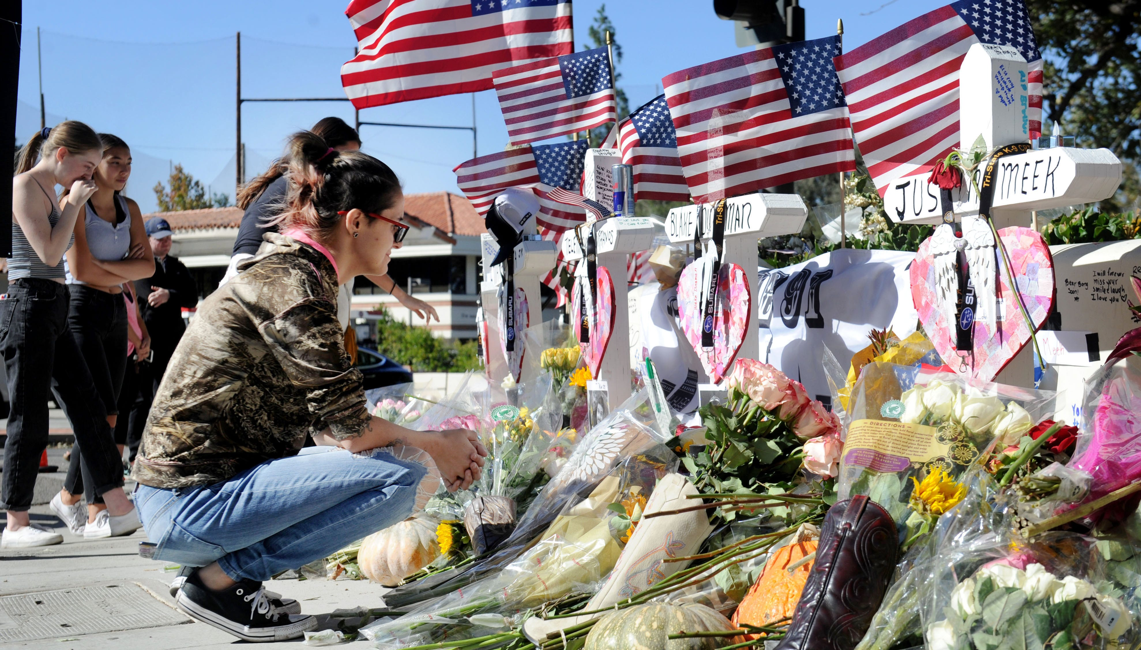 Mariah Piasecki kneels down and cries for her friends at a memorial set up near the Borderline Bar & Grill in Thousand Oaks. Twelve people were killed in a shooting Wednesday night at the bar.