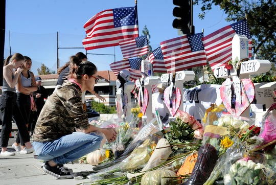 Mariah Piasecki kneels down and cries for her friends at a memorial set up near the Borderline Bar & Grill in Thousand Oaks. Twelve victims were killed in a Nov. 7 shooting at the bar.