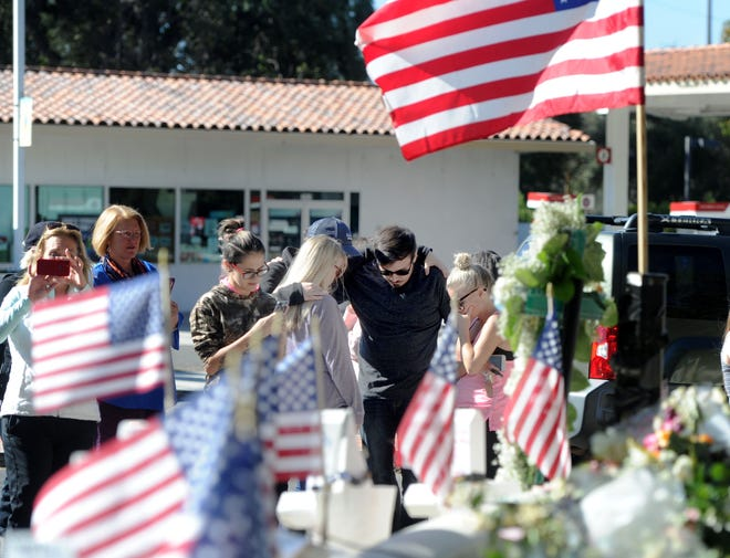 People pray at the Borderline Bar & Grill memorial in Thousand Oaks. Twelve people were killed in a Nov. 7 shooting at the country bar.