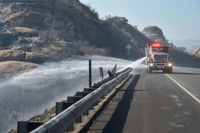A truck sprays water over the burning embers along Highway 118 near Rocky Peak Road on Monday as firefighters battle a brush fire that burned close to 100 acres. The Peak Fire broke out as firefighters continued to battle the Hill and Woolsey fires.