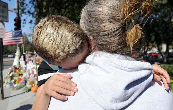 Cheryl Tate hugs her son Chayse Tate as they look at a cross for son Cody Gifford-Coffman near the Borderline Bar & Grill in Thousand Oaks. Coffman was one of 12 killed by a gunman Nov. 7.