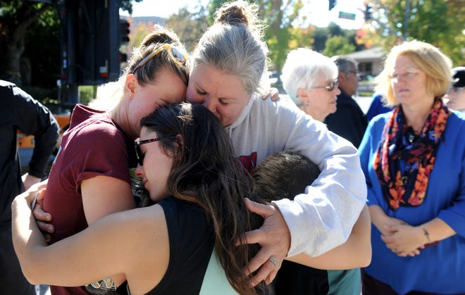 (Left to Right) Anna Berg and Devin Milligan hug Cheryl Tate and her son, Chayse Tate, Monday near the Borderline Bar & Grill in Thousand Oaks where a memorial was set up for the victims of Wednesday's night's shooting. Tate's son, Cody Coffman, was one of those killed.