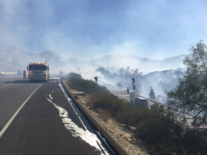 Firefighters attack a blaze that sparked Monday morning at Rocky Peak near Simi Valley. The fire briefly closed Highway 118 to traffic in Simi Valley.