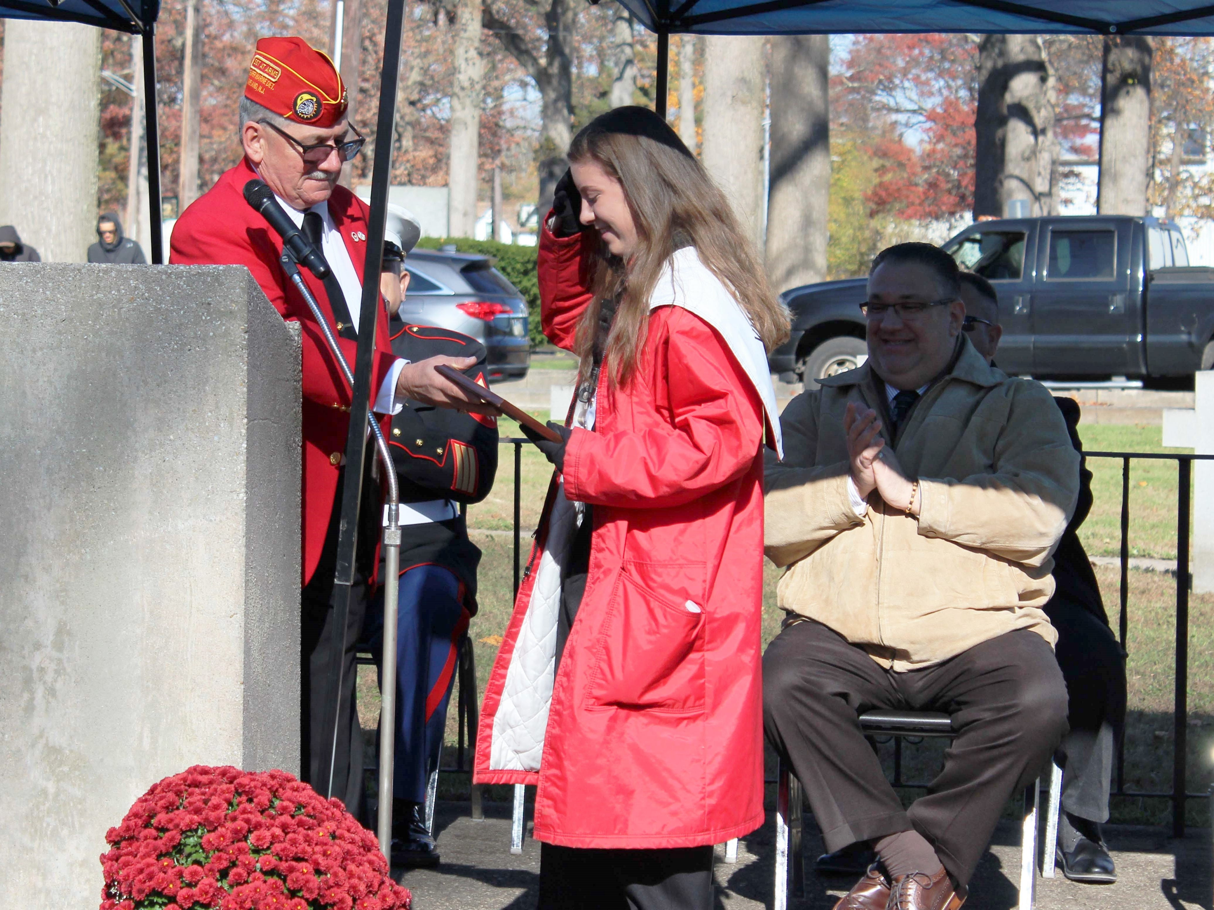 Robert Tesoroni Jr., President of the United Veterans Council of Vineland, presents Vineland High School junior, Alexandra Brodzik, with a plaque honoring her efforts for the veterans of Vineland.