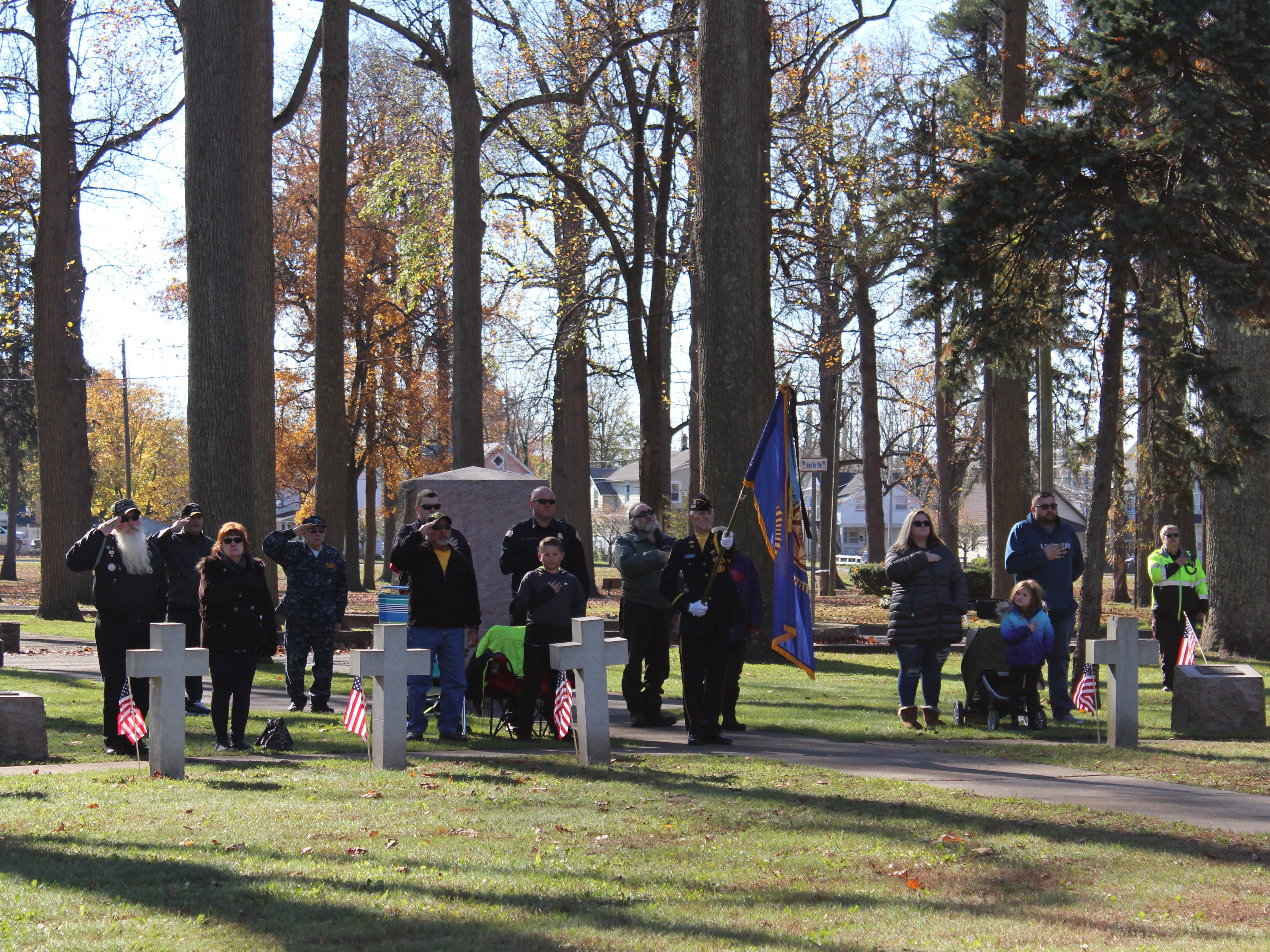 Some of the attendees of the Veterans Day ceremony at Landis Park on Sunday morning stand near the World War I monument during the national anthem.