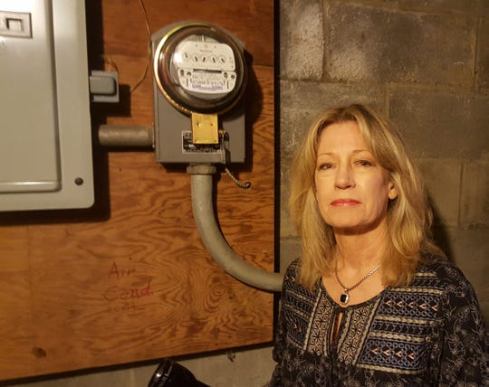 Lisa Price stands next to her analog meter.