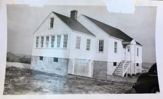 This photo shared by Carol Orr shows her home as it was built in 1946. Since then, sand and the addition of top soil has buried most of the concrete foundation seen here.