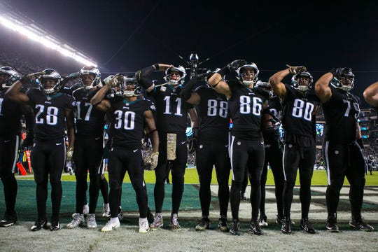 The Philadelphia Eagles offense salute the crowd during a Zach Ertz (86) touchdown celebration Sunday night against the Cowboys at Lincoln Financial Stadium.