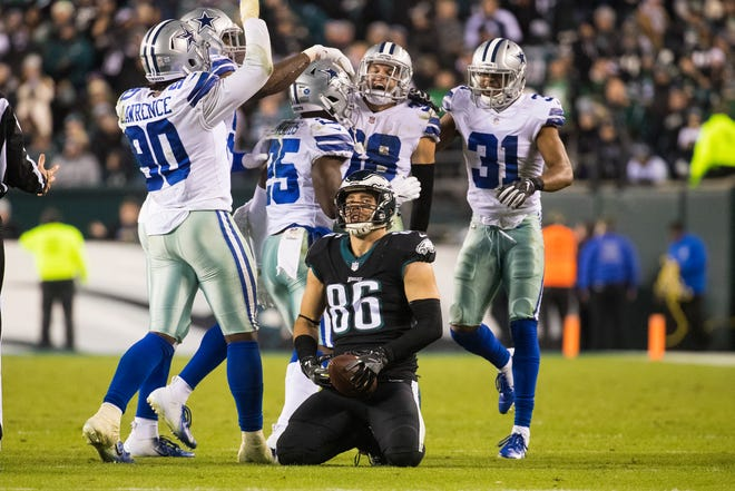 Eagles' Zach Ertz (86) sits after coming up short on fourth down as the Dallas Cowboys celebrate behind him Sunday night at Lincoln Financial Field. The Eagles lost to Cowboys 27-20.