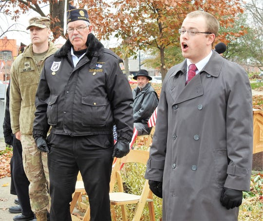 Zac Miller and Gary Kilpatrick stand as Samuel Scott sings the theme song for the U.S Army during a Veterans Day ceremony Monday on the Coshocton Court Square.