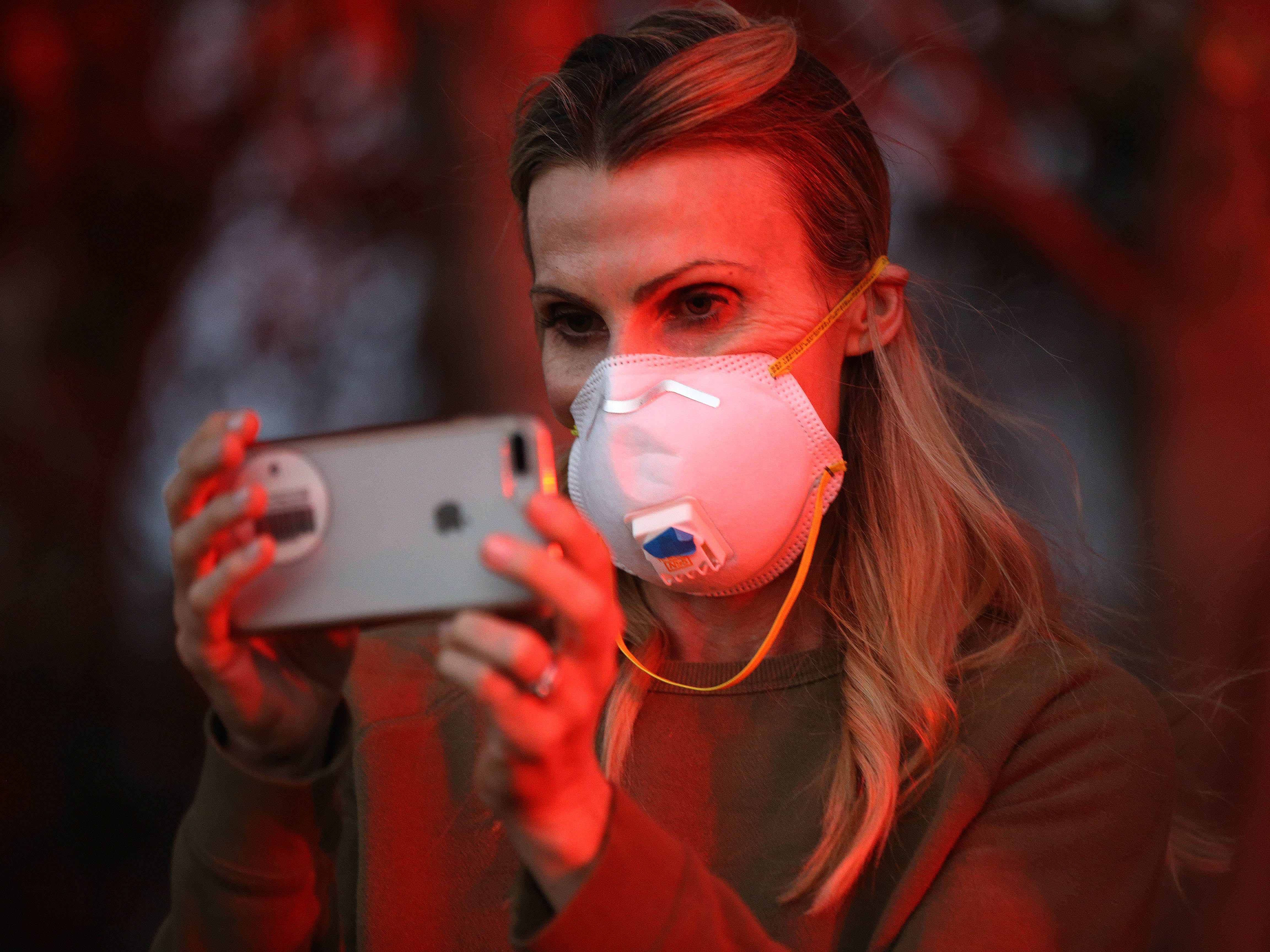 Disa Grant watches firefighters battle flames from the Woolsey Fire on Nov. 11, 2018, in Westlake Village, Calif.