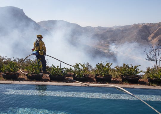 A firefighter looks out from the swimming pool in the backyard of a saved home after extinguishing a flare-up of the Woolsey Fire in West Hills, California.
