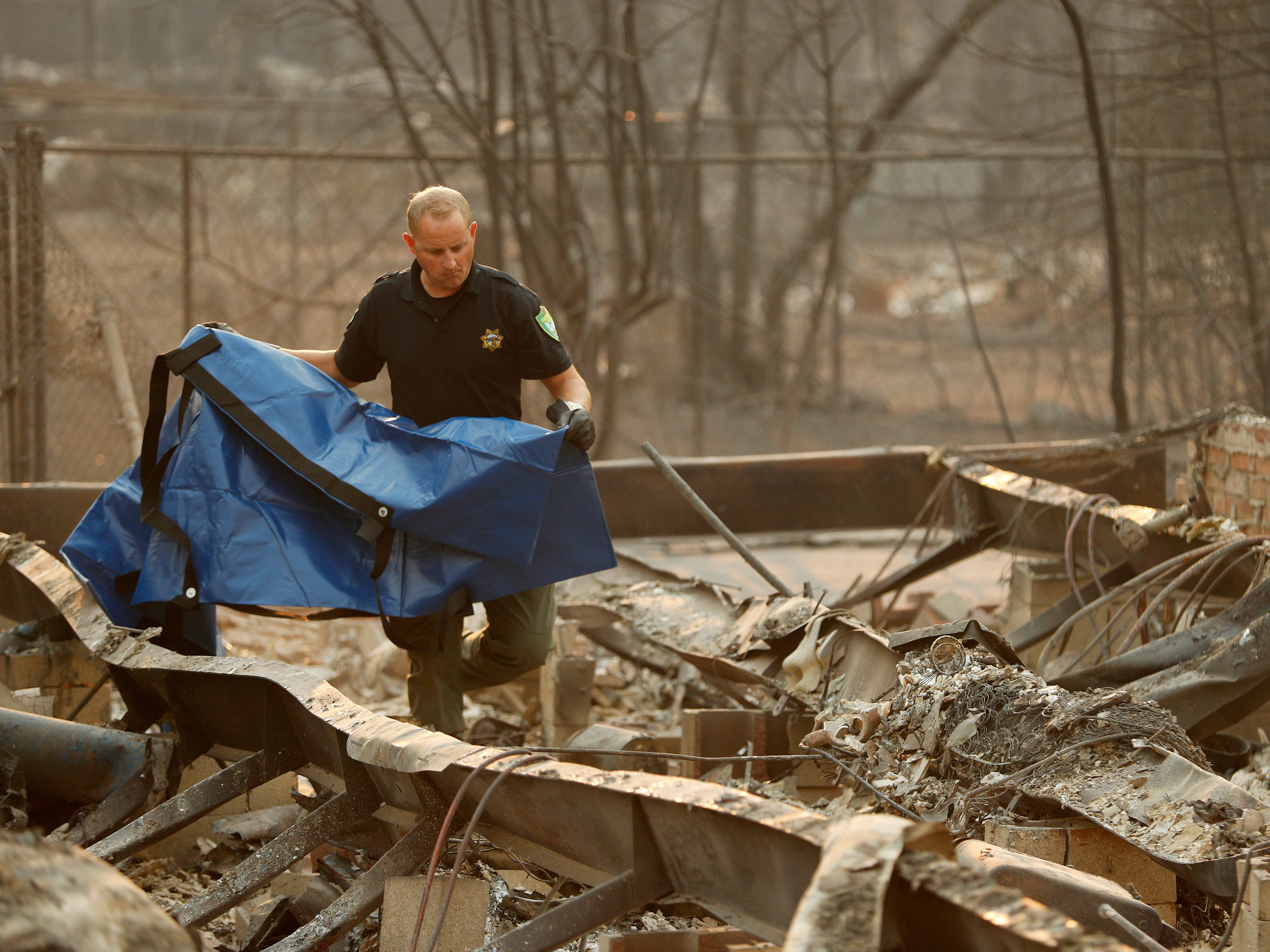Sgt. Nathan Lyberger of the Yuba County Sheriff Department, prepares a bag to move human remains found at a burned out home at the Camp Fire on Nov. 11, 2018, in Paradise, Calif.
