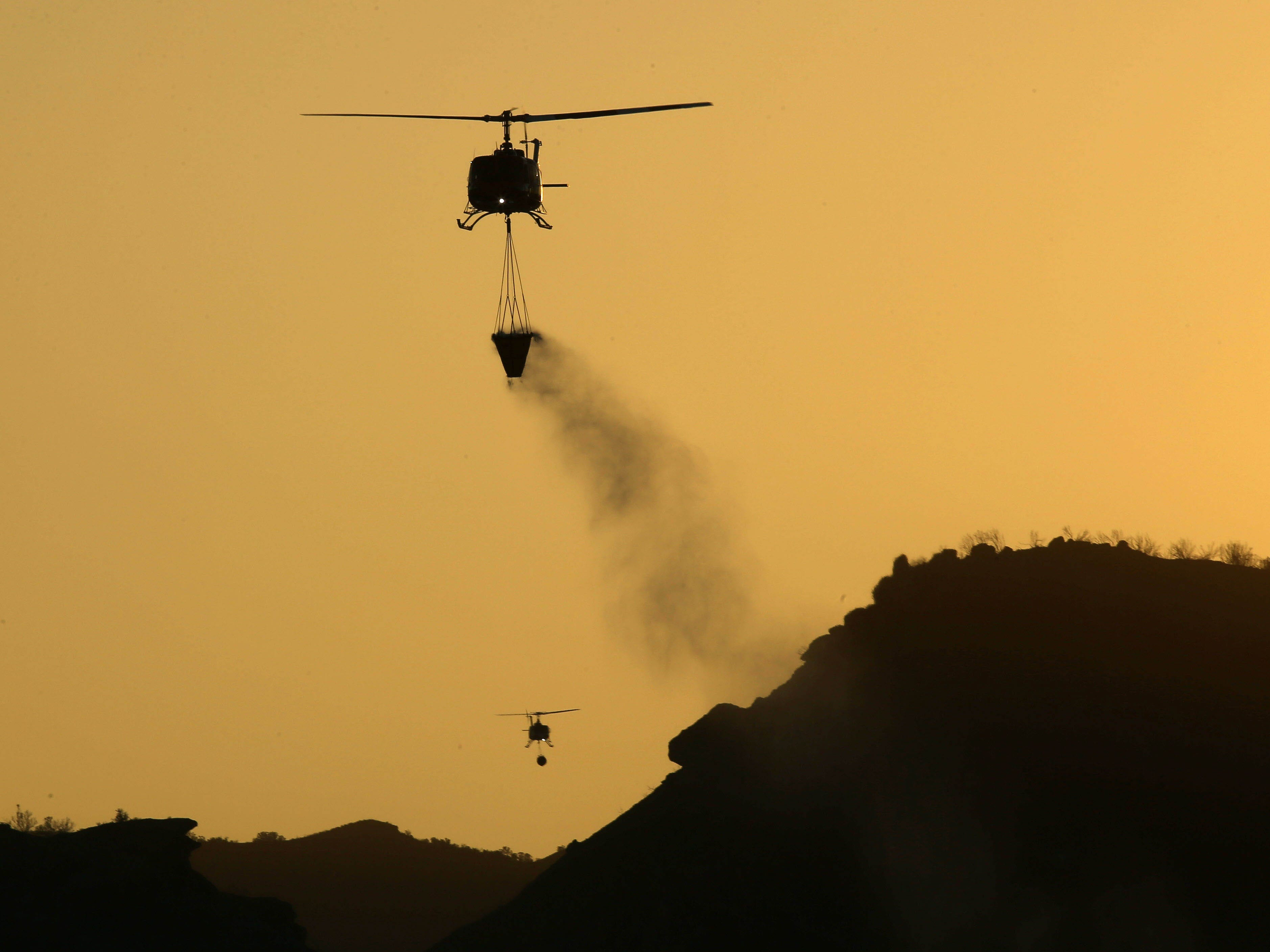 Nov 11, 2018; Westlake Village, CA, USA; A helicopter prepares to drop water on flames from the Woolsey Fire on Nov. 11, 2018, in Westlake Village, Calif.