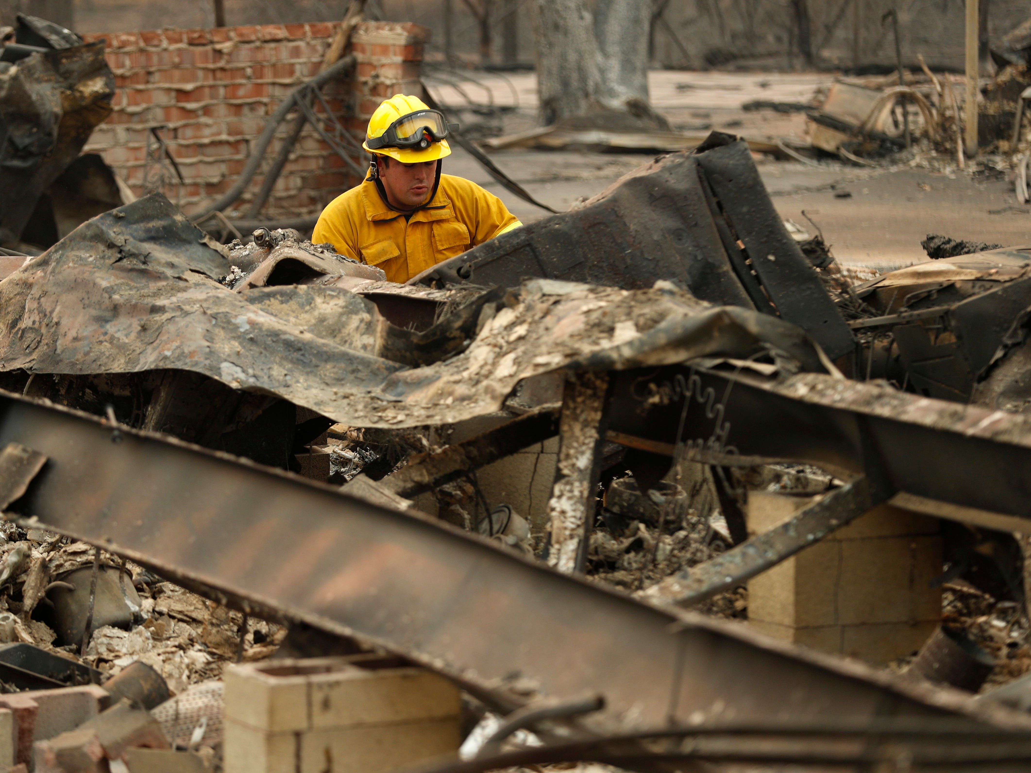 A firefighter looks through a home destroyed by the Camp Fire where human remains were found on Nov. 11, 2018, in Paradise, Calif.