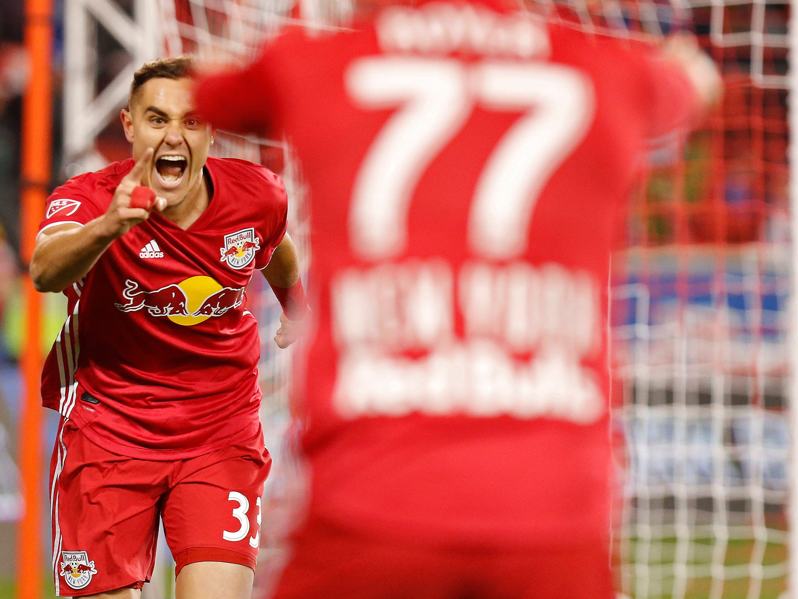 New York Red Bulls defender Aaron Long (33) celebrates with teammate Daniel Royer after scoring a goal against Columbus Crew SC in the first half in the Eastern Conference semifinal at Red Bull Arena.