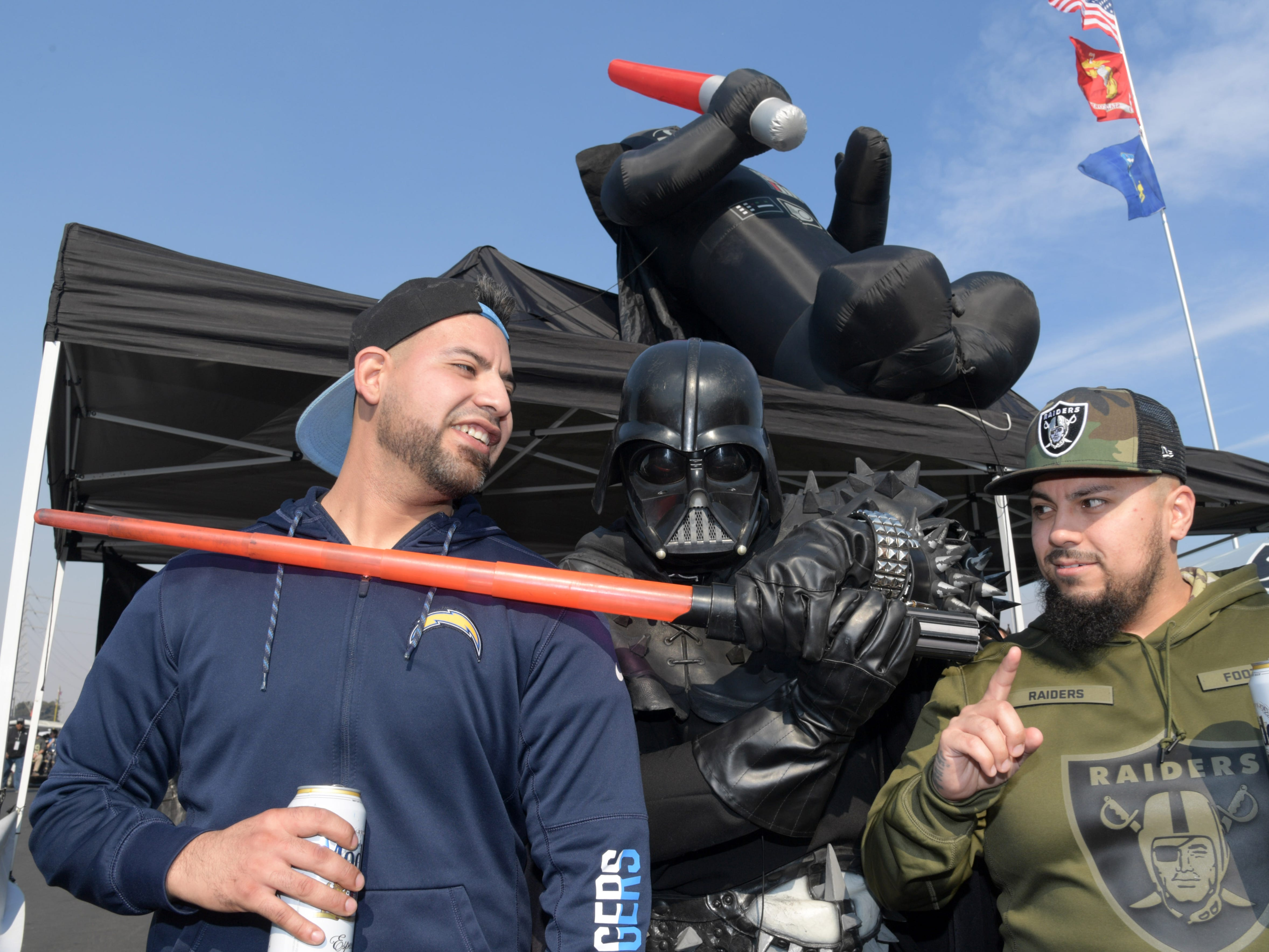 "Los Angeles Chargers fans pose with an Oakland Raiders fan dressed as ""Star Wars"" character Darth Vader at Oakland Coliseum."